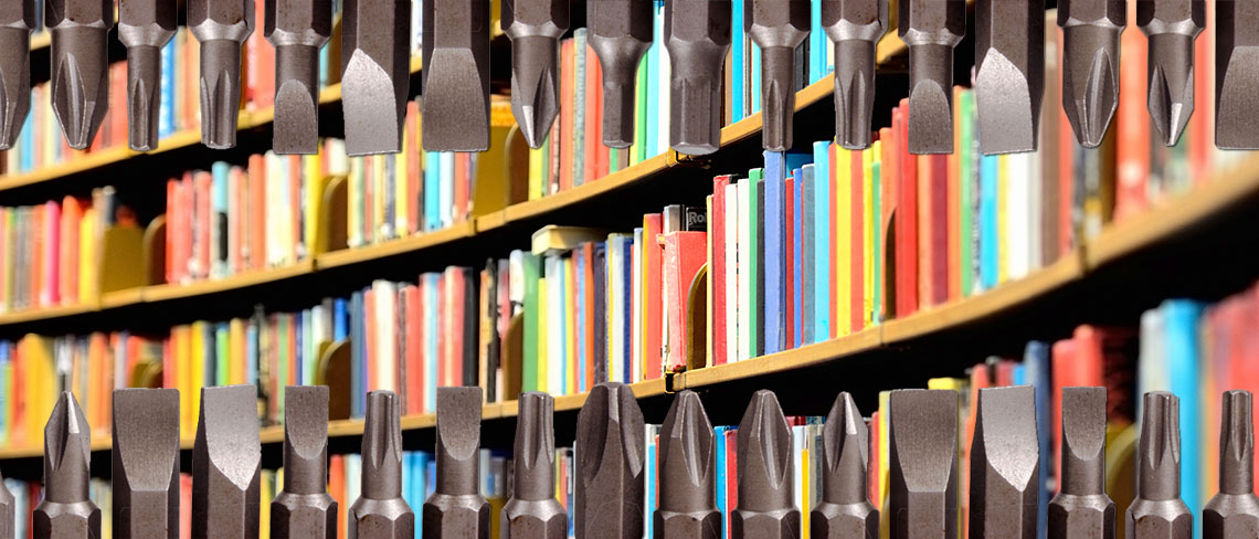 A curving library bookshelf with colorful books behind a horizontal trim of drill bits at the top and bottom of the frame