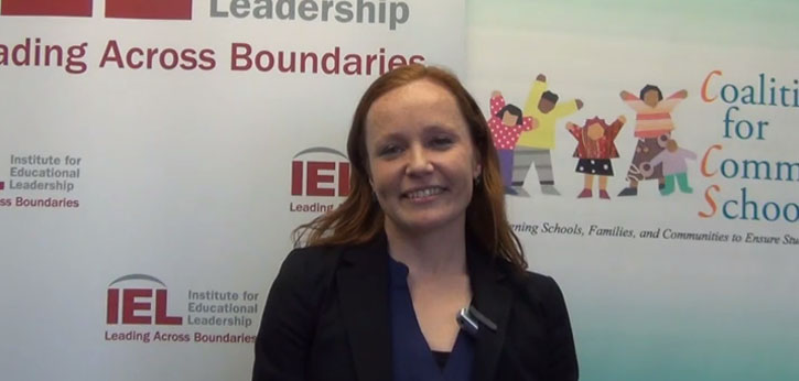 IEL's Coalition for Community Schools(CCS) Public Policy Manager Mary Kingston Roche speaks in front of the IEL and CCS logos.