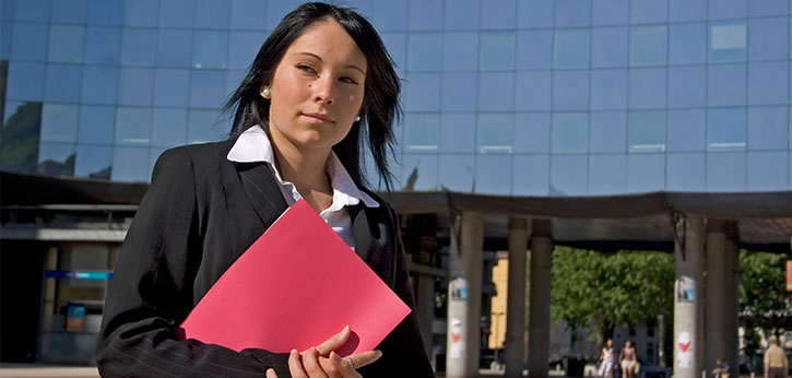 A young woman in business attire prepares to start an internship.