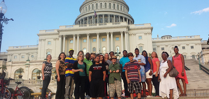 A group of youth and mentors from IEL's career-focused Ready to Achieve Mentoring Program for youth with disabilities stands on the steps of the U.S. Capitol.