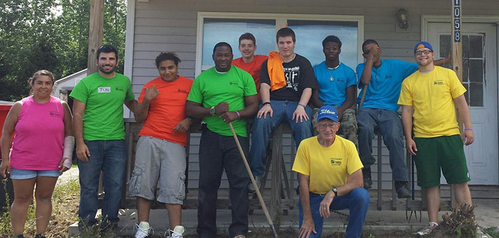 A group of youth, mentors, and staff from Peckham, the Right Turn site in Lansing, Michigan pose for a group photo during a restorative justice community service project winterizing homes for the elderly.