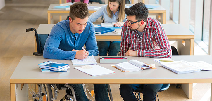 Two college students, one of whom uses a wheelchair, study in their school's library.