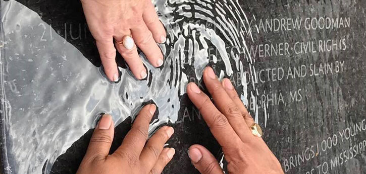 At a memorial for those lost in the civil rights movment, three hands touch the names through the memorial's shallow water.
