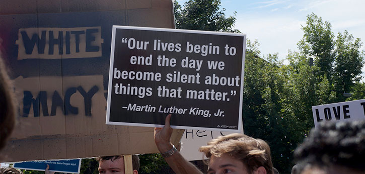 """A protestor in Charlottesville holds up a sign with a Martin Luther King Quote: """"Our lives begin to end the day we become silent about things that matter."""""""