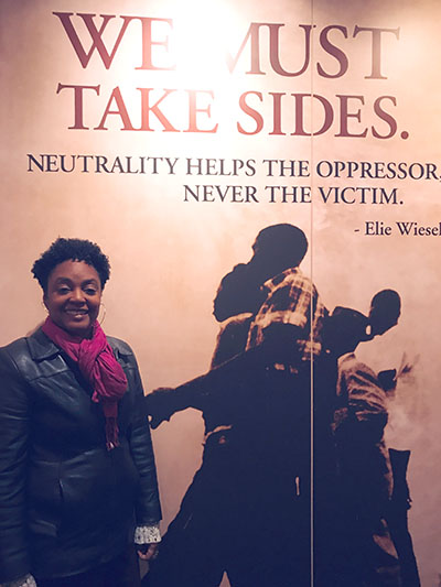 """IEL Civil Rights Bus Tour participant Lucretia Murphy poses next to an image with an Elie Wiesel quote: """"We must take sides. Neutrality helps the oppressor, never the victim."""""""