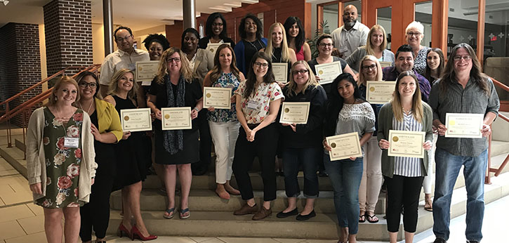 A diverse group of Ontario youth service professionals pose with their training certificates.