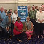 A group of Appalachian Higher Education Network annual conference attendees post around conference signage.