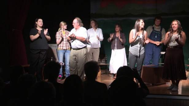 Community members from multiple generations perform together on stage