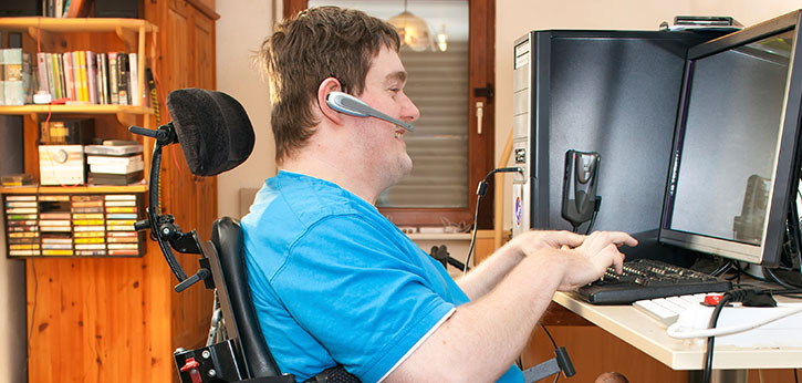 Young man in wheelchair working on a computer with a headset.