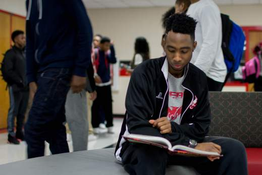 A young black man sits and reads at school