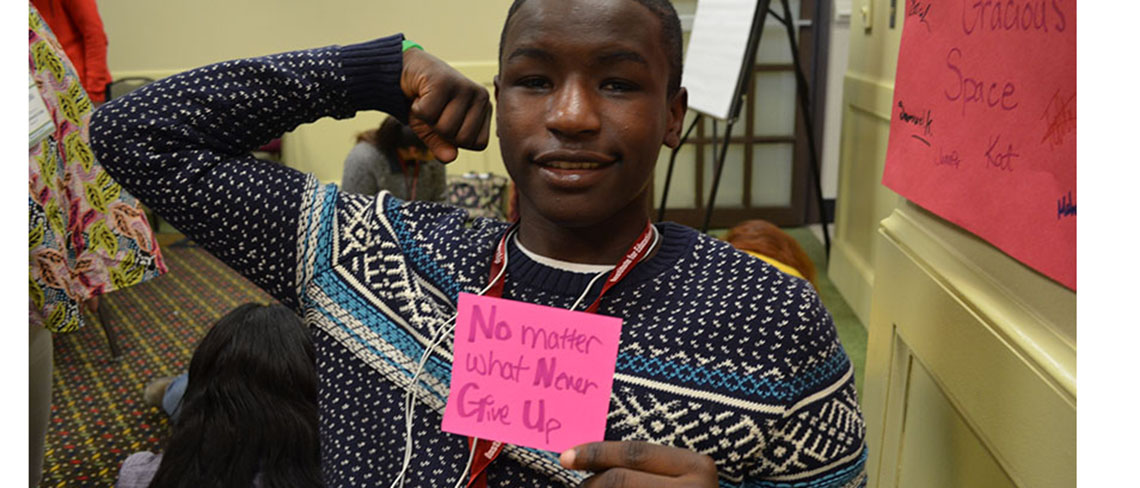 """Student holds up a post it with the words """"no matter what never give up"""""""