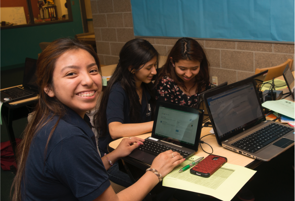 Students sit at a table working on laptops