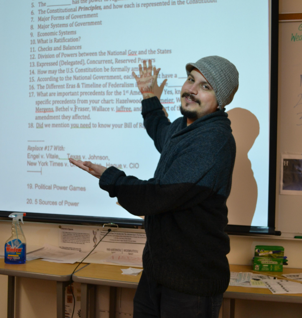 Teacher stands in front of a whiteboard pointing at the screen