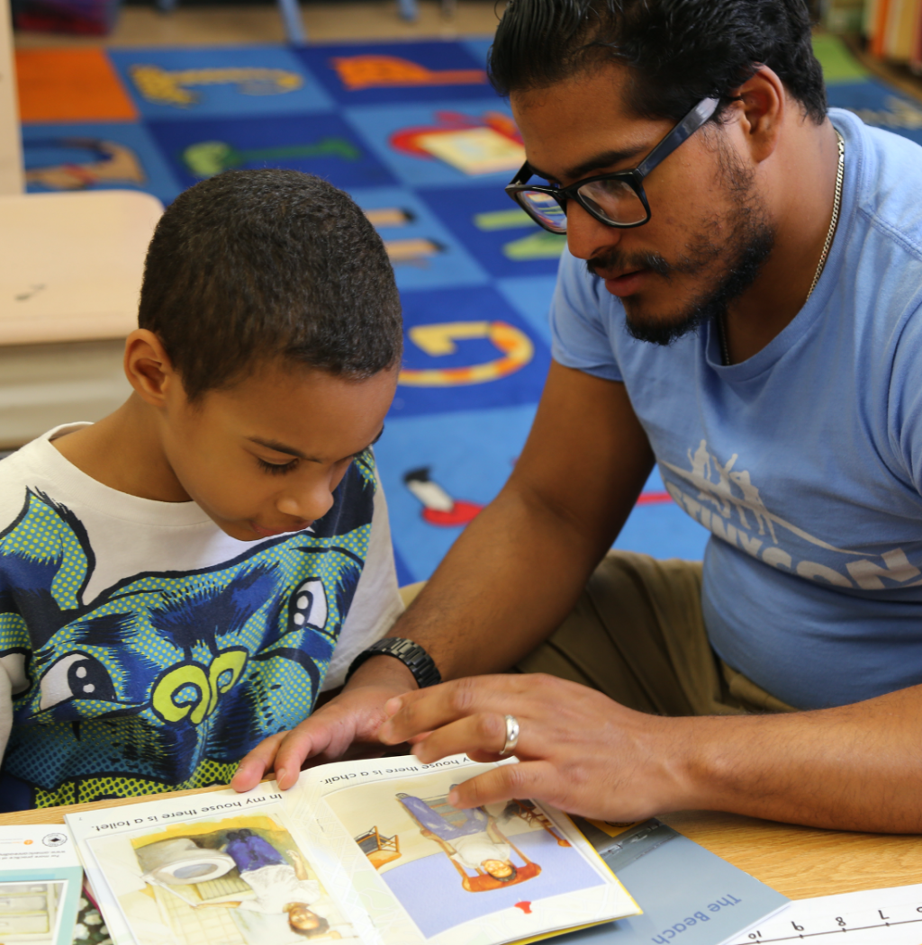 Teacher and student read a book together
